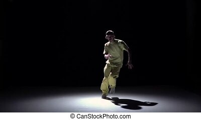 Breakdance dancer in yellow suit starts dance on black,...