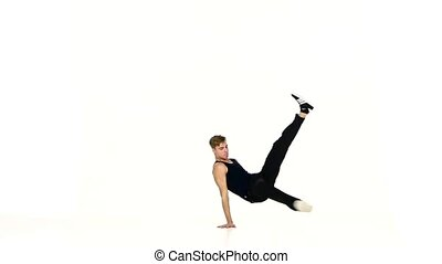 Young man in black suit continue dancing breakdance, white,...