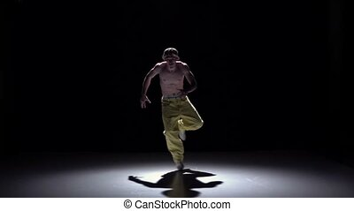 Breakdance dancer in yellow pants dance on black, shadow,...