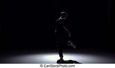 Young blonde dancer man dancing breakdance on black, slow...