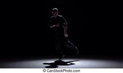 Dancer in dark suit dancing breakdance, on black, shadow,...