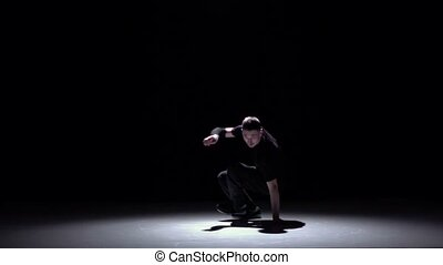 Cool breakdance style dancer starts dance, on black, shadow,...