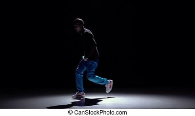 Modern breakdance man in blue trousers dancing, black,...