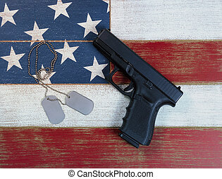 Pistol and ID tags with USA national flag colors painted on faded wooden boards