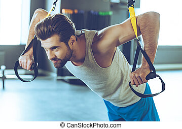 Strength and concentration. Young handsome man in sportswear exercising at gym