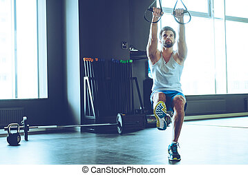 Great TRX workout. Full length of young handsome man in sportswear exercising at gym