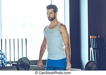 Concentrated athlete. Young handsome man in sportswear lifting barbell at gym