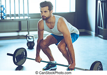 Lifting barbell. Young handsome man in sportswear lifting barbell at gym