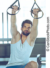 Balance and motivation. Young handsome man in sportswear exercising at gym
