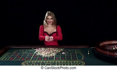 Winning woman tossing up chips. Black. Slow motion