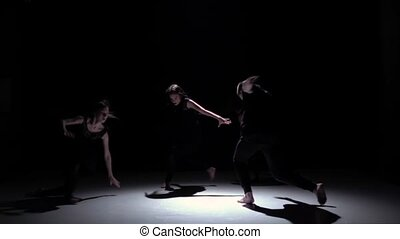 Contemporary dance of four talanted dancers on black, shadow, slow motion