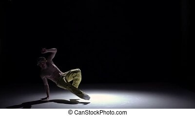 Breakdance man in cap and yellow trousers dancing breakdance on black, shadow, slow motion