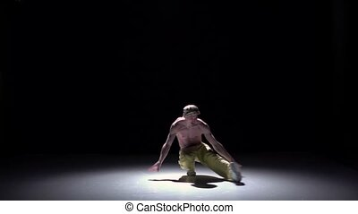 Breakdance man in cap and yellow trousers starts dancing breakdance on black, shadow, slow motion