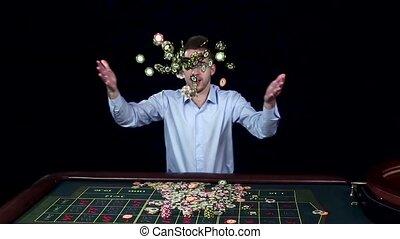 Man smiles hugely as tosses winnings in the air. Black