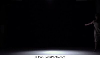 Modern dancer girl in white dress dancing contemporary, whirls on black, shadow, slow motion