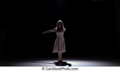 Modern dancer girl in white dress dancing contemporary on black, shadow, slow motion