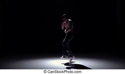 Breakdance man in cap dancing breakdance on black, shadow,...