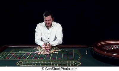 Man tossing gambling chips in a casino. Black. Slow motion -...