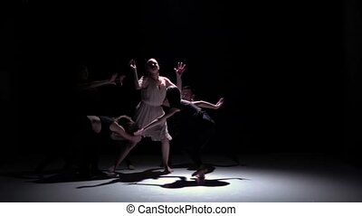 Contemporary dance performance of five talanted dancers on black, shadow, slow motion
