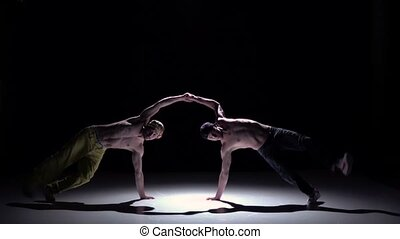 Two dancers performing and continue dance breakdance on black, shadow, slow motion