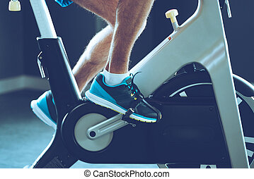 Intense cardio workout. Side view close-up part of young man in sports shoes cycling at gym