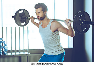 Lifting weight. Young handsome man in sportswear lifting barbell at gym