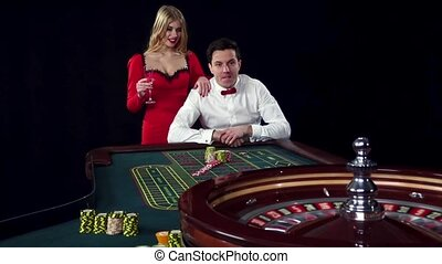 Couple playing roulette wins at the casino Black - Couple...