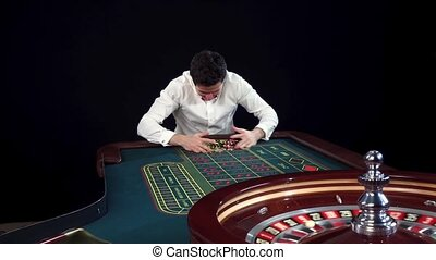 Man winning at roulette table in casino. Black