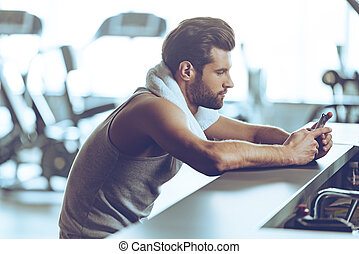 Staying in touch at gym Side view of handsome young men in...