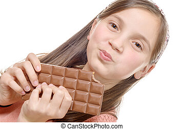 preteen girl eats chocolate, isolated on white - a preteen...