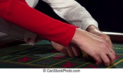 Gambler stakes playing roulette at the roulette table. Black