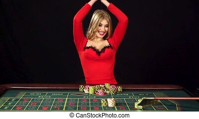 Young beautiful girl has won in poker, black, slow motion -...