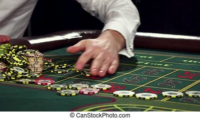 Poker players with chips at green casino table Black -...
