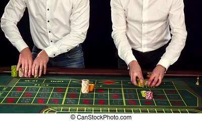 Young cute guys dressed formally playing roulette. Black -...