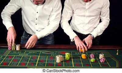 Two young men in suits behind gambling table. Black