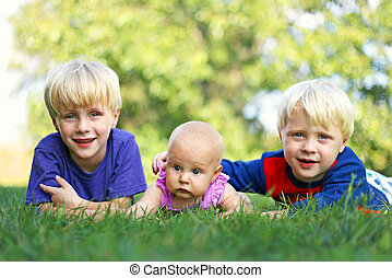 Brothers and Baby Sisters Relaxing Outside - Portrait of...