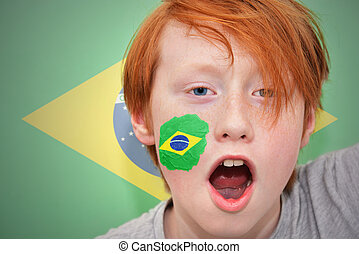redhead fan boy with brazilian flag painted on his face on...
