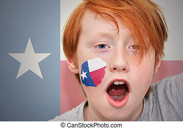 redhead fan boy with texas state flag painted on his face.