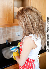 Caucasian woman doing the dishes at home