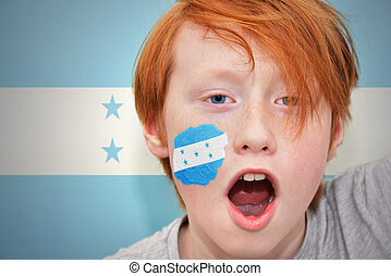 redhead fan boy with honduran flag painted on his face. on...