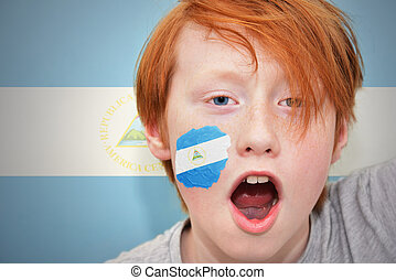 redhead fan boy with nicaraguan flag painted on his face on...