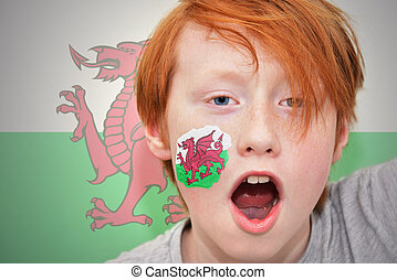 redhead fan boy with welsh flag painted on his face. on the...