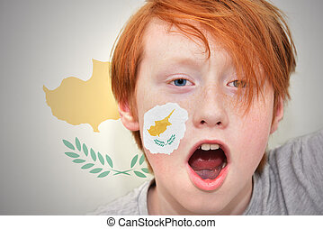 redhead fan boy with cypriot flag painted on his face on the...