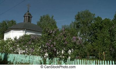 View of church and churchyard with blooming lilac - View of...