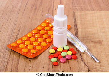 Pills, thermometer and nose drops and for colds, treatment...