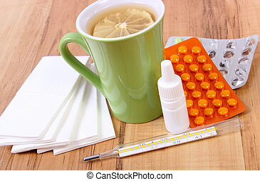 Pills and nose drops for colds, handkerchiefs and hot tea...