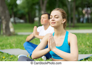 Young couple meditating on green grass - Young man and woman...