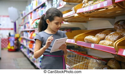 girl teen from tablet with in supermarket to buy baking food...