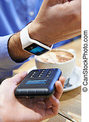 Man Paying In Coffee Shop Using Contactless Payment App On...
