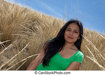 Attractive Latin Woman in a field with grass
